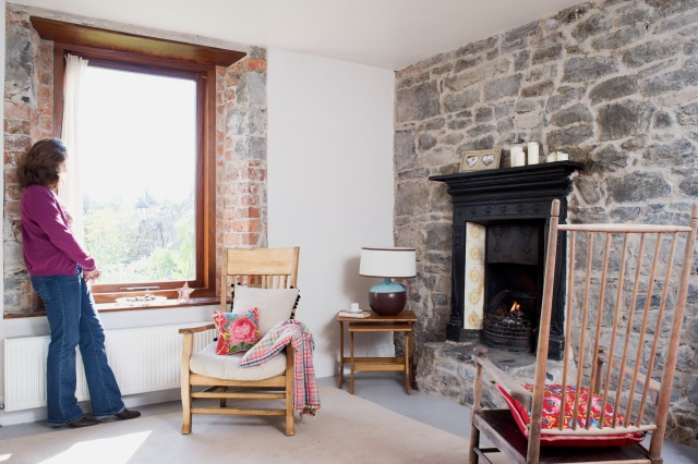 Iona Limerick Private Residence-fire place stone wall window timber reveals live area painted cement floor
